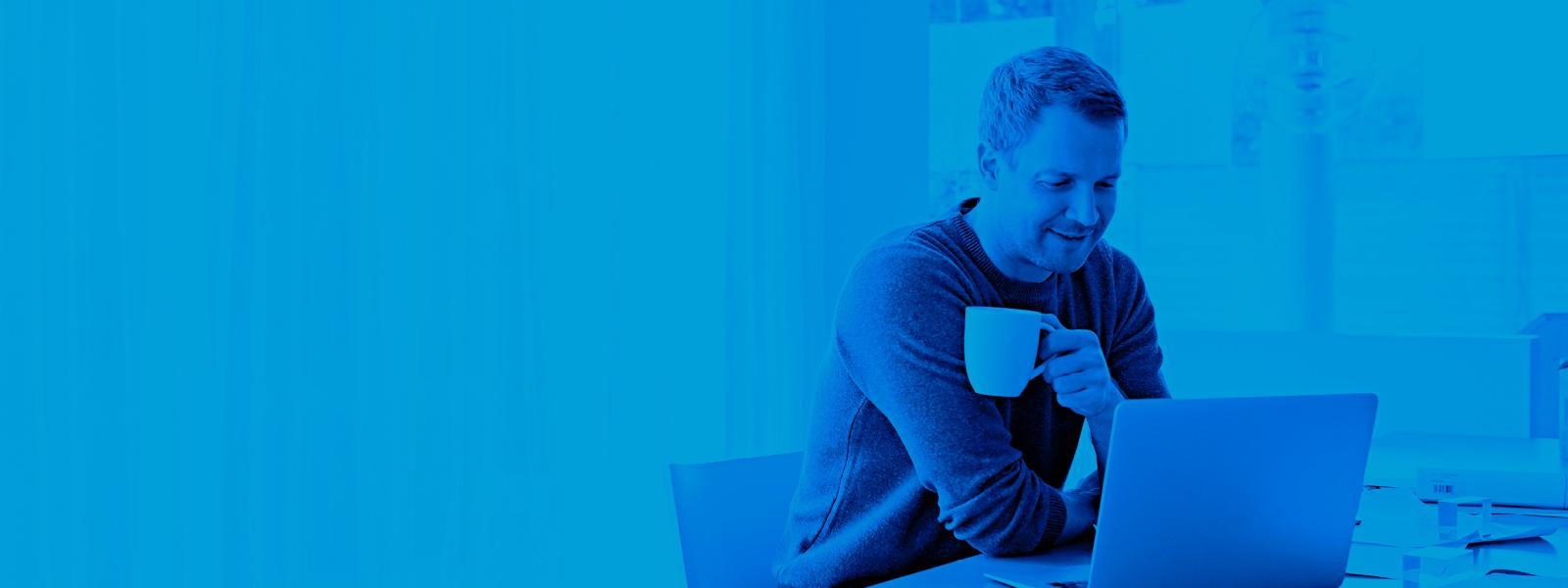 Imagen de un hombre tomando café mientras trabaja.